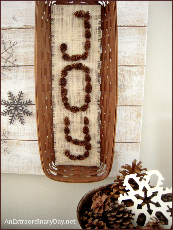 Handmade JOY art from pine cones and burlap in a basket