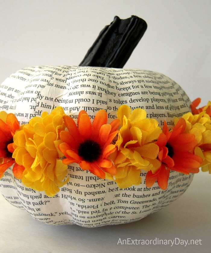 Create a flowery book page pumpkin by decoupaging an artificial pumpkin with book pages and ringing it with flowers to spark many happy smiles.