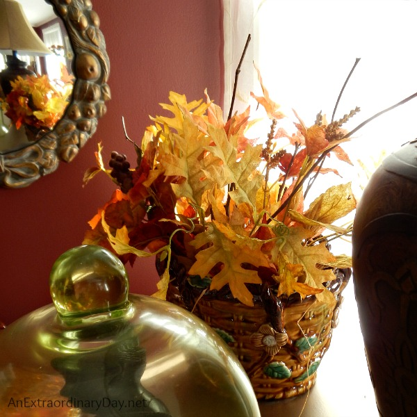 A majolica basket filled with faux leaves and tips for dressing a living room for fall.