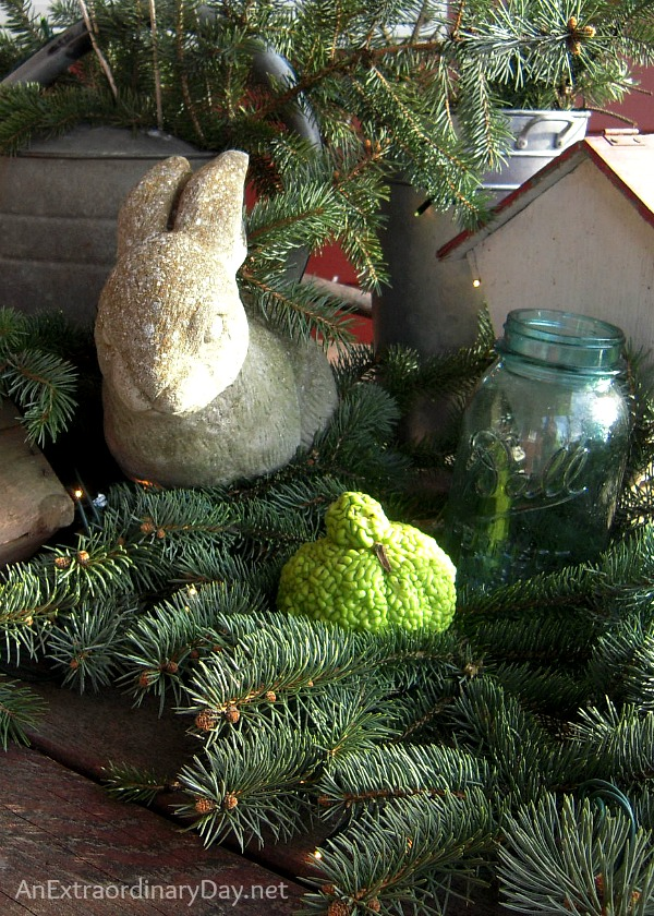 Gathering of greens and a stone rabbit in a Christmas vignette at AnExtraordinaryDay.net