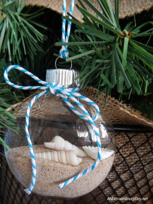 Beach and shells in a clear glass Christmas ornament on this Coastal Christmas Tree Dressed up with Fresh Flowers