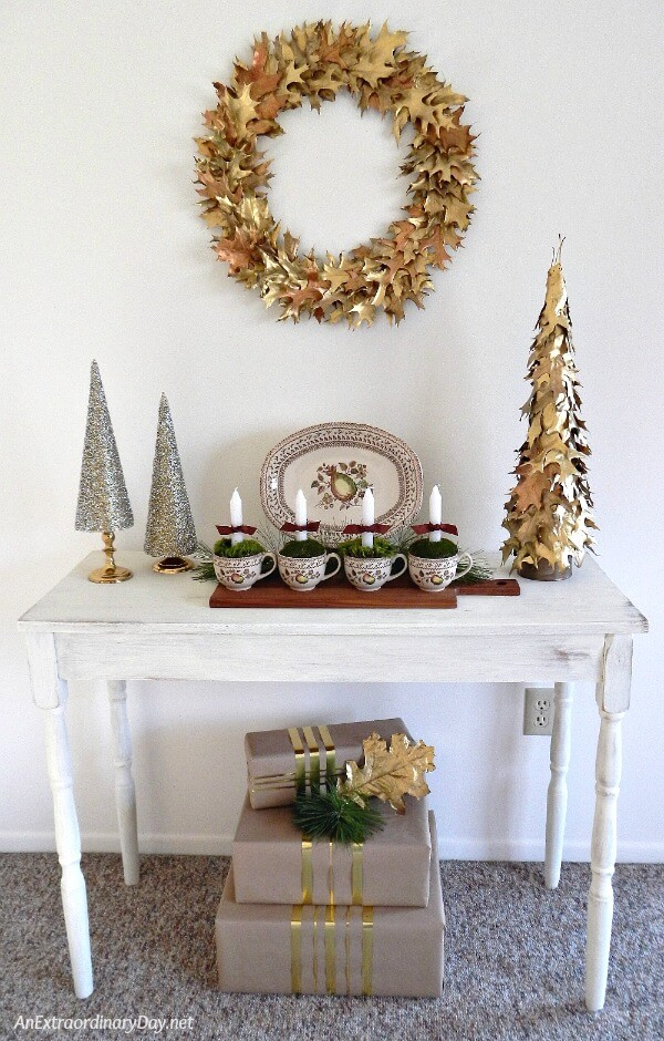 Handcrafted gold oak leaf wreath and trash to treasure table with Advent candles