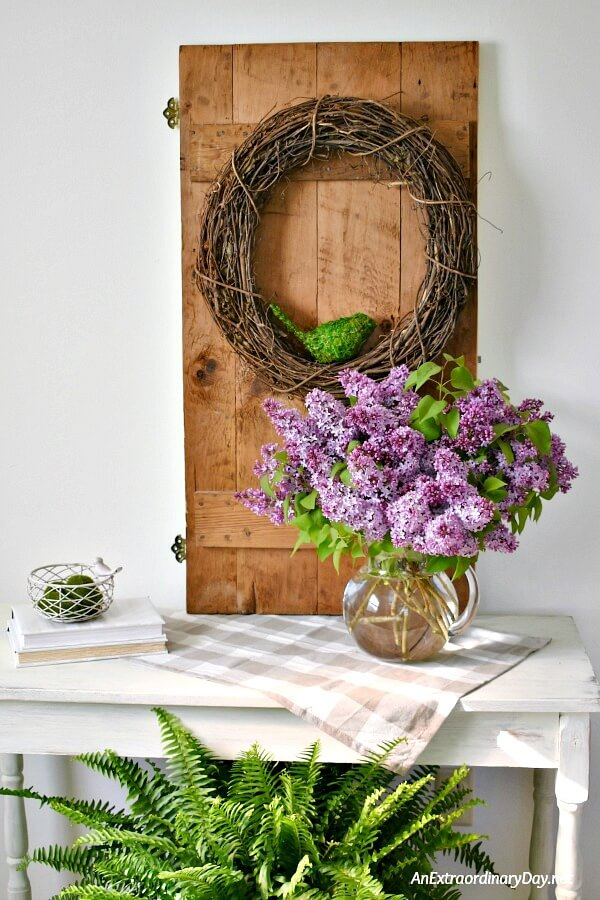 Create pretty seasonal home decor for spring with beautiful vignette showcasing an old door, a grapevine wreath, and a huge bouquet of lilacs. It makes a lovely rustic farmhouse style decor statement. - AnExtraordinaryDay.net