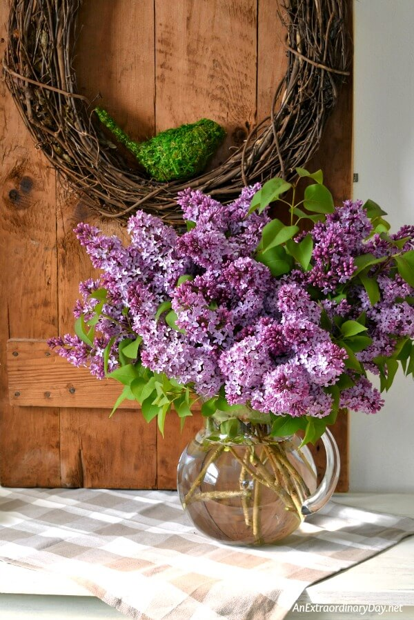 Create pretty seasonal home decor for spring with beautiful vignette showcasing an old door, a grapevine wreath, and a huge bouquet of lilacs. It makes a lovely rustic farmhouse style decor statement.